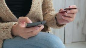 Ходить по магазинам женщины онлайн на smartphone с кредитной карточкой Стоковые Изображения