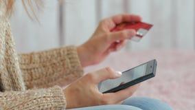 Ходить по магазинам женщины онлайн на smartphone с кредитной карточкой Стоковые Фотографии RF