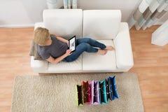 Ходить по магазинам женщины онлайн с таблеткой цифров Стоковое фото RF