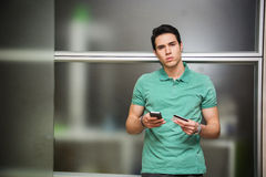 Ходить по магазинам молодого человека онлайн на мобильном телефоне Стоковое Изображение RF