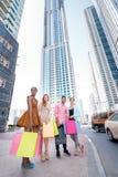 ходить по магазинам совместно 4 друз держа хозяйственные сумки в их h Стоковое Фото
