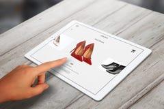 Ходить по магазинам с таблеткой Ботинки покупки женщины красные на онлайн рынке Стоковые Изображения RF