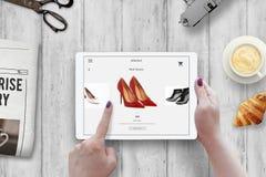 Ходить по магазинам с таблеткой Ботинки покупки женщины красные на онлайн рынке Стоковая Фотография