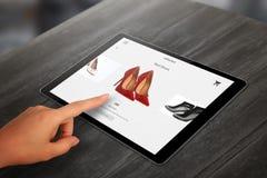 Ходить по магазинам с таблеткой Ботинки покупки женщины красные на онлайн рынке стоковое фото