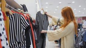 Ходить по магазинам для женщины Женщина смотря платье в клетке Стоковое Фото