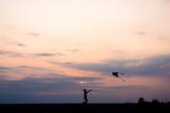 Ход мальчика силуэта и летать змей Стоковое Изображение RF