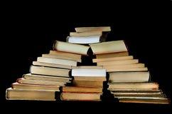 Холм старых книг на черноте стоковые изображения