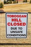 Холм Toboggan закрыл знак вывешенный в общественный парк как только весь снег плавил стоковая фотография
