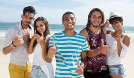 Холодная группа в составе многонациональный человек и женщины на пляже Стоковые Изображения RF