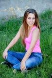 Холодная милая женщина сидя на траве стоковые фото