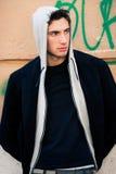 Холодная модель человека с hoodie, городской предпосылкой стены Стоковые Изображения