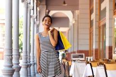 Холодная молодая чернокожая женщина идя с хозяйственными сумками Стоковая Фотография
