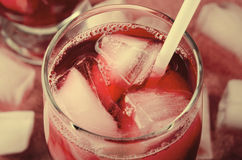 Холодное питье вишни с кубами льда и трубками коктеиля в стеклах, на розовой предпосылке Стоковые Фото