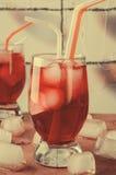 Холодное питье вишни с кубами льда и трубками коктеиля в стеклах, на розовой предпосылке Стоковая Фотография RF