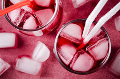 Холодное питье вишни с кубами льда и трубками коктеиля в стеклах, на розовой предпосылке Стоковое Фото