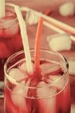 Холодное питье вишни с кубами льда и трубками коктеиля в стеклах, на розовой предпосылке Стоковые Фотографии RF