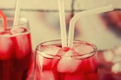 Холодное питье вишни с кубами льда и трубками коктеиля в стеклах, на розовой предпосылке Стоковое Изображение RF