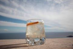 Холодное питье внутри она греет на солнце Стоковая Фотография