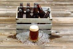 Холодное темное пиво с винтажной клетью заполнило с льдом - холодом разлитый по бутылкам b Стоковые Фотографии RF