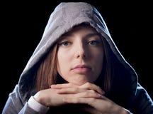Холодные девушка или молодая женщина подростка на ее 20s представляя холодный показывая клобук ориентации нося дальше Стоковое фото RF
