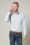 Холодный бизнесмен говоря на мобильном телефоне на серой предпосылке Стоковые Фотографии RF