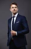 Холодный бизнесмен стоя на сером цвете Стоковая Фотография