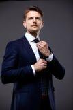 Холодный бизнесмен стоя на сером цвете Стоковые Изображения RF
