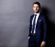 Холодный бизнесмен стоя на сером цвете Стоковое Фото