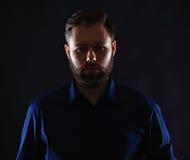 Холодный бизнесмен стоя на темной предпосылке градиента Стоковое Фото