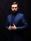 Холодный бизнесмен стоя на темной предпосылке градиента Стоковые Изображения