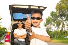 Холодный большой палец руки мальчика поднимающий вверх и отец через оружия с автомобилем стоковая фотография