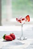 Холодный коктеиль с водочкой, сиропом клубники, свежими клубниками и задавленным льдом в стеклах на светлой предпосылке стоковое фото rf