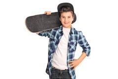 Холодный мальчик нося скейтборд Стоковое Фото