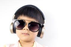 Холодный мальчик слушает к музыке с золотыми наушниками Стоковые Изображения RF