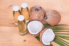 Холодный - отжатое дополнительное виргинское кокосовое масло в бутылках с кокосами Стоковое Изображение