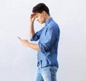 Холодный парень идя и смотря мобильный телефон Стоковая Фотография RF