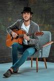 Холодный парень при шляпа играя гитару на серой предпосылке стоковые фото