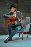 Холодный парень при шляпа играя гитару на серой предпосылке стоковое изображение