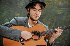 Холодный парень при шляпа играя гитару на серой предпосылке стоковые изображения
