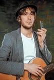 Холодный парень при шляпа играя гитару на серой предпосылке стоковые изображения rf