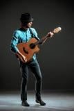 Холодный парень стоя с гитарой на темной предпосылке стоковые изображения