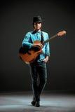Холодный парень стоя с гитарой на темной предпосылке стоковые изображения rf