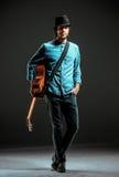 Холодный парень стоя с гитарой на темной предпосылке стоковые фотографии rf