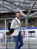 Холодный парень усмехаясь с сумкой на станции Стоковая Фотография