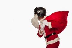 Холодный Санта Клаус с сумкой подарков в шлеме двигателей задняя часть белизны Стоковые Изображения