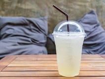 Холодный свежий лимонад на деревянном столе с предпосылкой подушки валика Стоковые Изображения