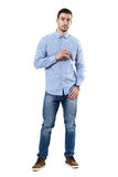 Холодный уверенно молодой умный вскользь бизнесмен держа солнечные очки смотря камеру Стоковое Фото
