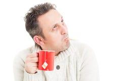 Холодный человек держа кружку и термометр в рте Стоковое Изображение