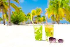 2 холодных вкусных коктеиля mohito и белых солнечные очки на белом песчаном пляже Стоковое Изображение RF