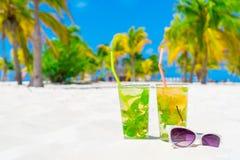 2 холодных вкусных коктеиля mohito и белых солнечные очки на белом песчаном пляже Стоковая Фотография